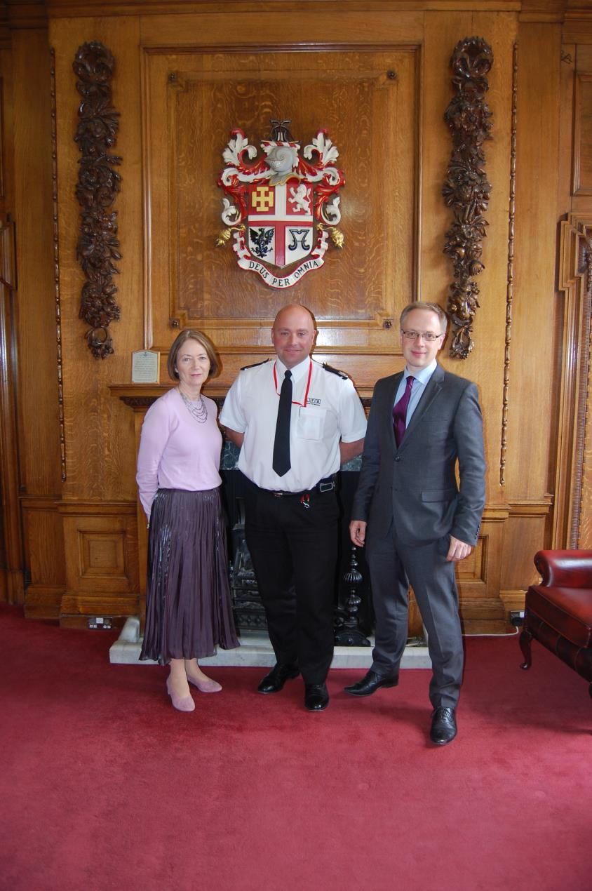 Paul Hobbs, London Fire Brigade's borough commander for Islington, centre, is greeted by Islington Council's chief executive Lesley Seary, left, and council leader Cllr Richard Watts, right.